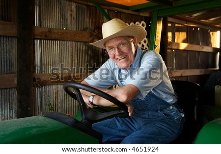 A farmer sitting on his tractor in the barn.