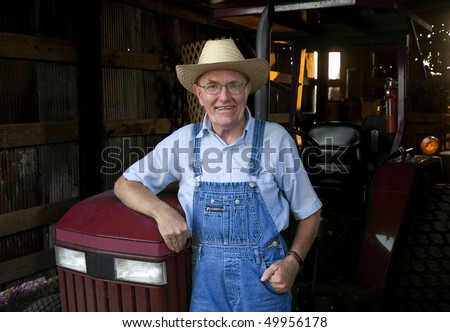 A farmer standing in front of his tractor in the barn.