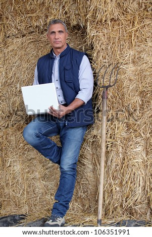 a farmer with a computer leaning against straw bales - stock photo