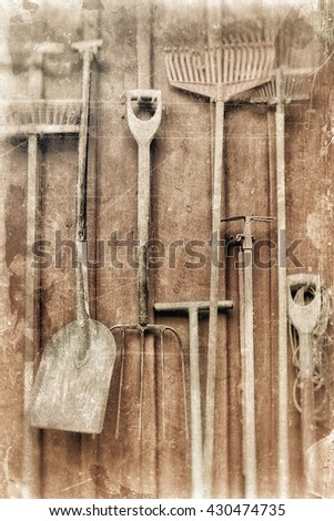 A farmers equipment hanging on a barn wall, textured in a multicolor style. - stock photo