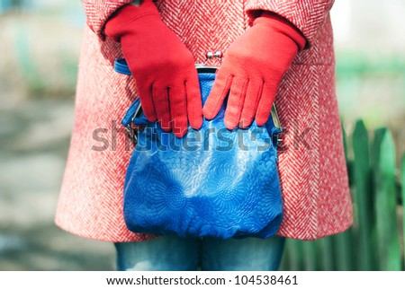 A fashion close up of a woman in a red spring-autumn wool topcoat, blue jeans and red gloves. Woman is holding a blue leather bag in her hands. On the background you can notice a green fence - stock photo