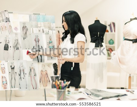 A fashion designer sorting out her new sketches.