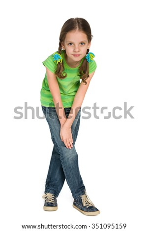 A fashion little girl is standing against the white background