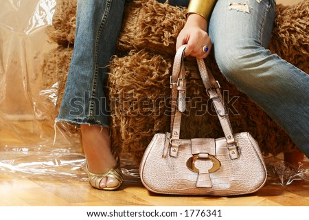A fashion shoot of the legs of a female model in jeans.  Model is holding a pink leather bag in her hand. - stock photo