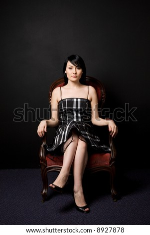 A fashion shot of a beautiful woman sitting on a vintage chair - stock photo