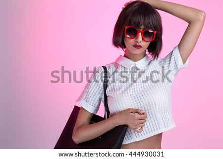 A fashionable young girl wearing sunglasses, showing off a black purse - stock photo