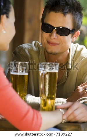 A fashionable young man enjoying a romantic drink with his female partner - stock photo