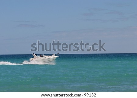 A fast boat cruises across the ocean in front of a beach.