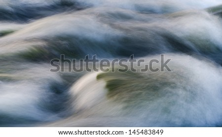 A fast flowing river shot with long exposure for milky effect. - stock photo