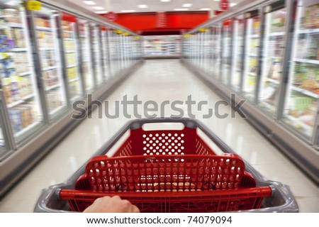 A fast food concept motion blur shot of a shopping trolley being pushed down the aisle of a supermarket