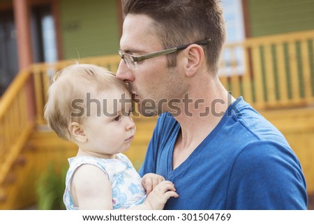 A father and daughter play in front of the house - stock photo