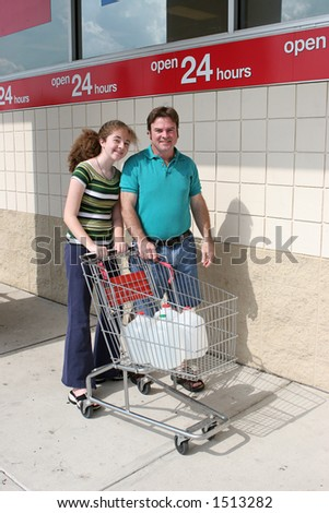 A father and daughter shopping for hurricane supplies.  Their cart is full of water jugs. - stock photo