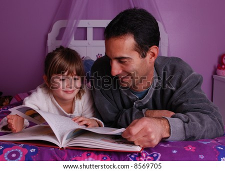 A father and daughter spend time reading a book - stock photo
