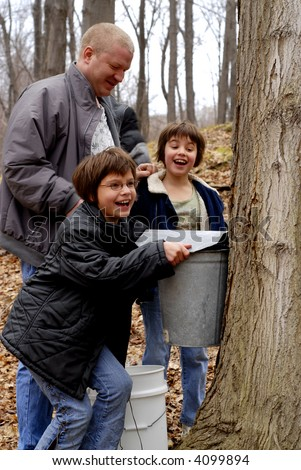 A father and daughters surprised by the amount of sap in the collection bucket of a tree while maple sugaring in late winter. - stock photo