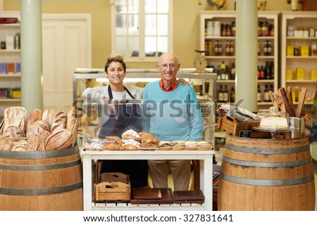 A father and daugther standing together in their deli - stock photo