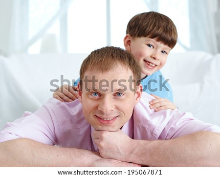 A father and his cute son lying on the floor and looking at camera - stock photo