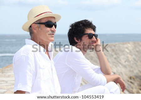A father and his son looking at the sea. - stock photo