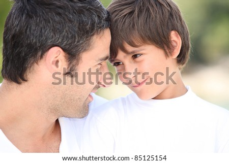 a father and his son looking each other in the eyes - stock photo