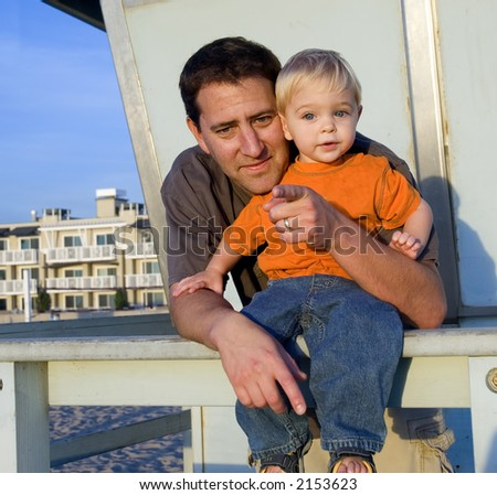 a father and his son together at the beach - stock photo
