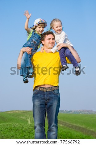 A father and his two daughters on the nature - stock photo