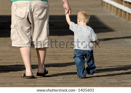 A father and his young son walk hand in hand.