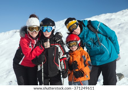 a father and mother with two boys in ski resort on a sunny day - stock photo