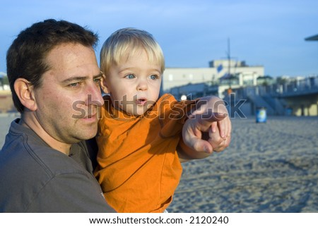 A Father and Son are at the beach having fun. - stock photo