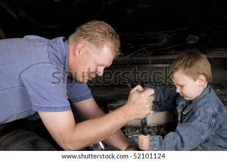 A father and son working together restoring an engine. - stock photo