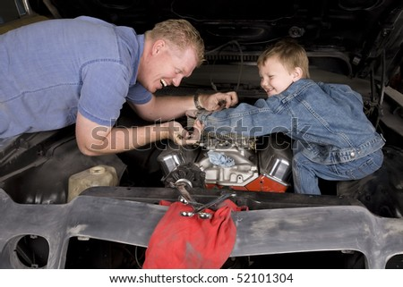 A father and son working together restoring an engine, with happy expressions on their faces. - stock photo