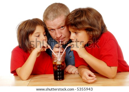 A father and two daughters drinking soda from one glass using 3 different straws. - stock photo