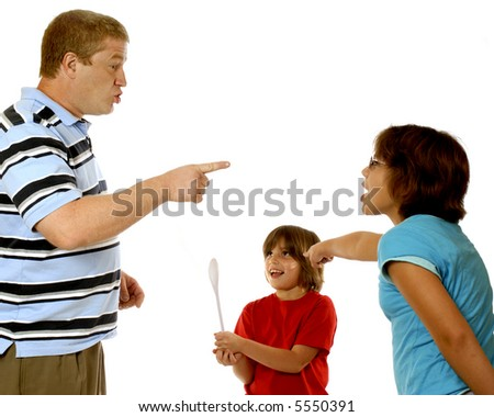 A father attempting to discipline his daughter.  She points the finger a blame at her little sister.  This smiling girl holds up a large spoon, hoping it will be used on her accuser. - stock photo
