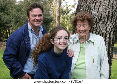 A father, daughter and grandmother at the park together.