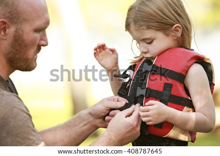 A father helping his daughter with her life jacket - stock photo