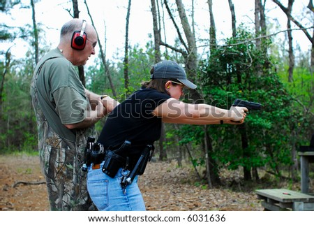 A father helping time his daughter's shooting practice. - stock photo