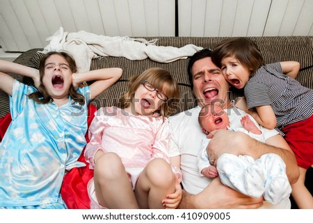 A father, his three daughters, and baby boy lean back on the couch with open mouth screams.