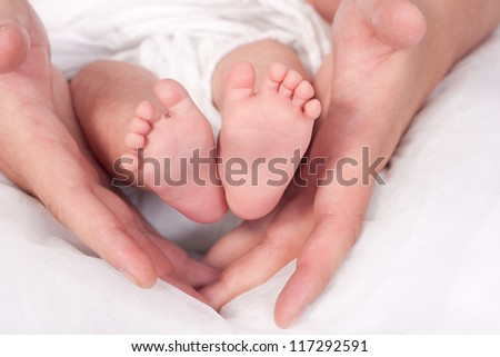 A father hold the feets of his newborn baby