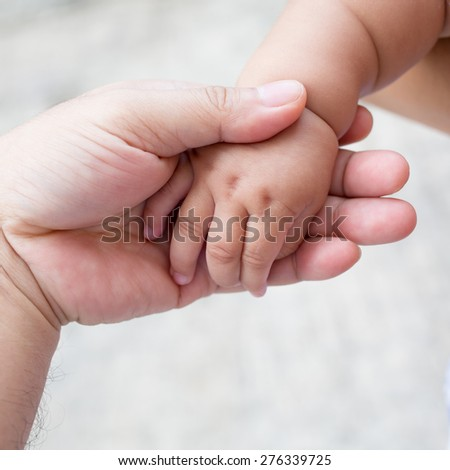A father hold the the feets of his new born son - stock photo
