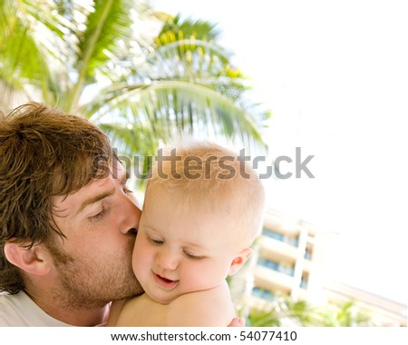 A father holds and kisses his baby son, with a muted tropical setting in the background and white space for copy. - stock photo