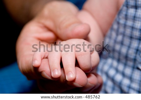 A father holds his baby's hand