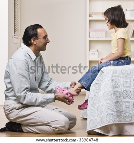 A father is helping his baby daughter with her shoes.  They are smiling and looking each other.  Square framed shot. - stock photo