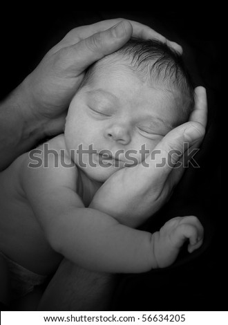 A father is holing a baby newborn in his hands. The infant is sleeping and it is a black and white portrait. The image can represent security, innocence or parenthood. - stock photo