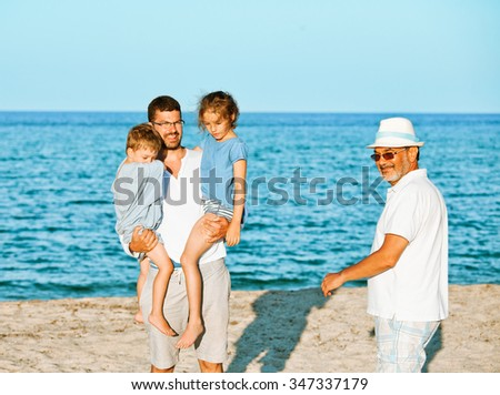 A father is lifting brother and sister kids on the seashore while grandfather is approaching with a smile.