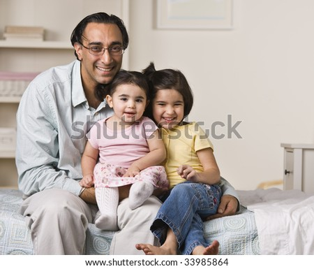 A father is sitting on a bed with his two young daughters.  They are smiling at the camera.  Horizontally framed shot. - stock photo
