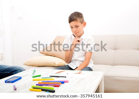 A father is sitting on the couch while his son is drawing.