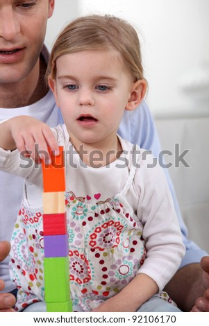 A father playing with her daughter. - stock photo