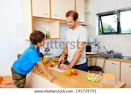 a father preparing his son's lunch while his son watches him across the kitchen counter - stock photo