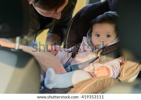 A father putting his baby daughter into her car seat in the car - stock photo