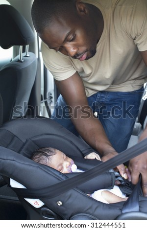 A father putting his newborn daughter into her car seat in the car. He is wearing casual clothing and looking at his daughter. - stock photo