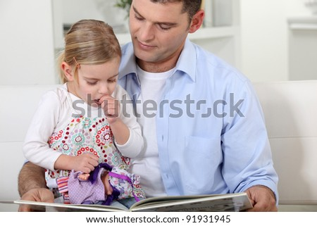A father reading to her daughter. - stock photo