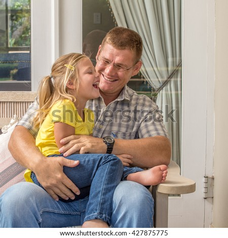 A father sits on a bench on the porch of his house while having fun with his young daughter who is sitting in his lap. - stock photo